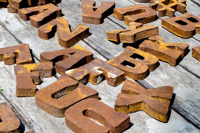 rusty metal letters sit on worn wood planks at an outdoor market Brown Close-up Day English Letters Metal Metal Letters Outdoors Photograpghy  Rusty Rusty Letters Wood Planks Words
