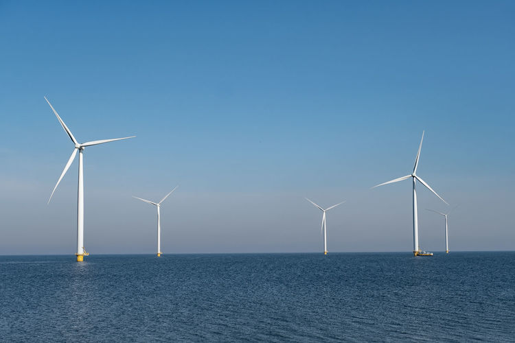 Wind turbines in sea against clear blue sky