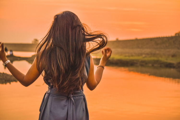 Rear view of woman with long hair standing by lake against sky during sunset
