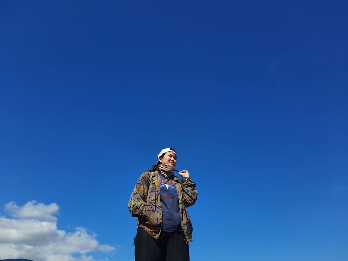 Low angle view of woman holding smart phone against blue sky
