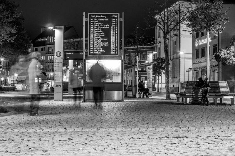 Building Exterior City Night Architecture Illuminated Street Built Structure City Life Men Real People Seat Group Of People Communication Blurred Motion Footpath Incidental People Lifestyles Transportation Cafe People Outdoors