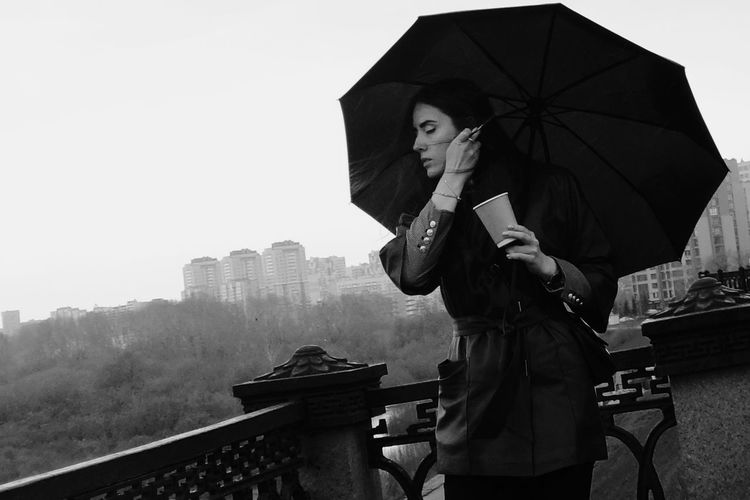 Architecture Building Exterior Built Structure City Day Girl Holding Leisure Activity Lifestyles Nature One Person Outdoors Protection Rain Rainy Season Real People Security Sky Standing Streetphotography Three Quarter Length Umbrella