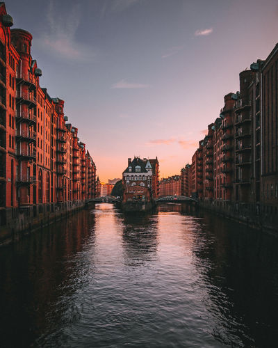 Canal amidst buildings in city during sunset
