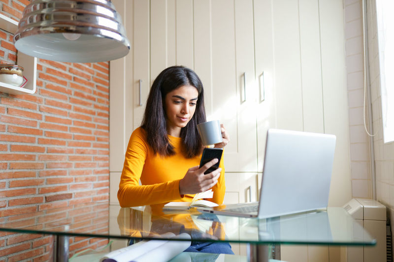 Young woman using phone while sitting by table in office