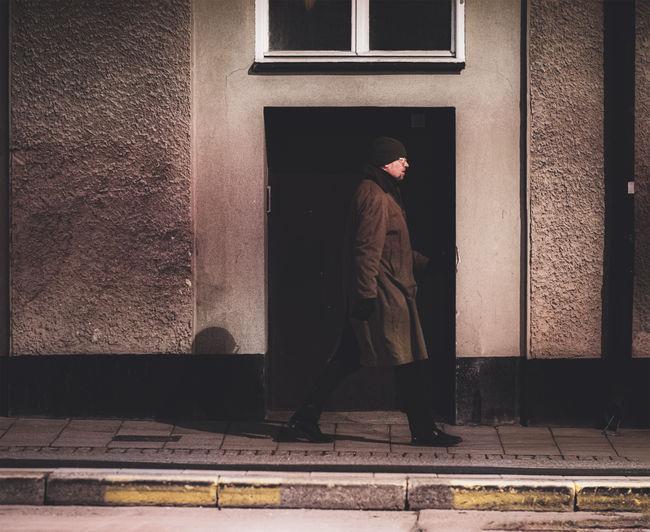 Rear view of man walking on sidewalk against building