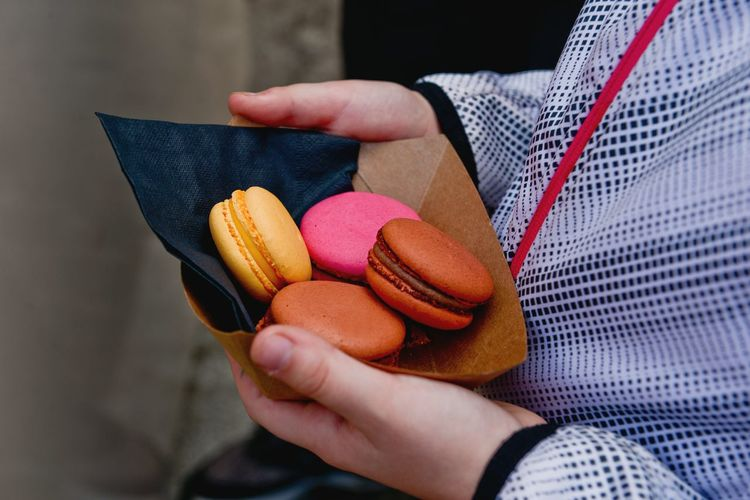 Cropped image of person holding macaroons
