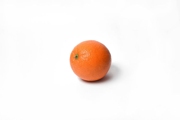 Close-up of orange apple against white background