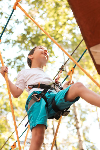 Cute boy 8 years old in adventure rope town Adventure Boy Casual Clothing Day Enjoyment Extreme Sports Focus On Foreground Forest Freedom Fun Land Leisure Activity Lifestyles Low Angle View Men Nature One Person Outdoors Playground Real People Rope Rope Town Safety Harness Tree Be Brave