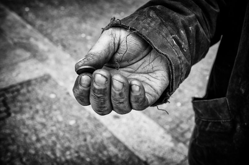 Cropped Hand Of Beggar Holding Coin On Footpath