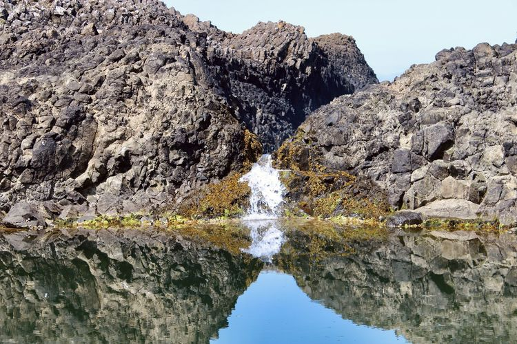 Reflection of rocks in water against clear sky