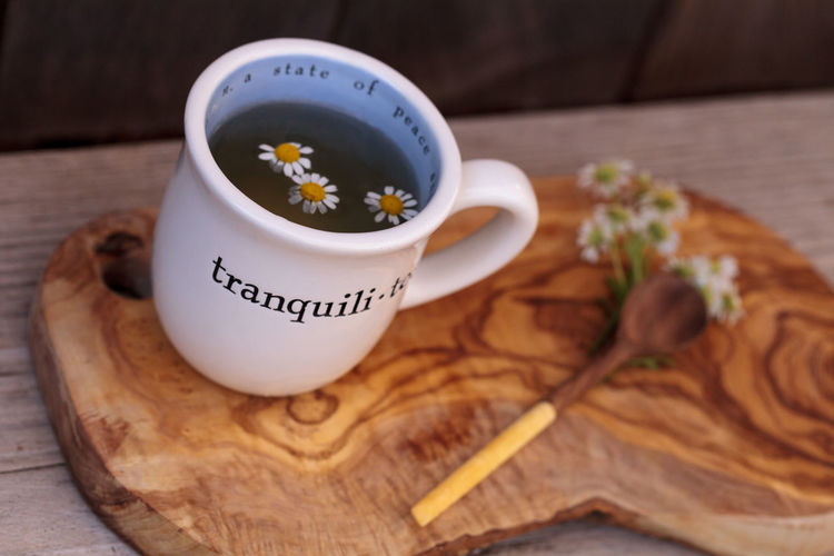 High angle view of daisies with chamomile tea in cup on cutting board over table