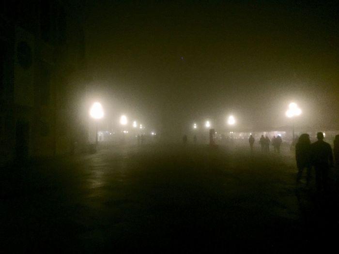 Silhouette people walking on illuminated street at night