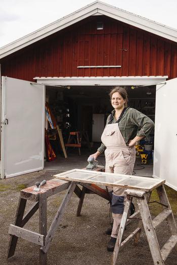 Portrait of a smiling woman standing against built structure
