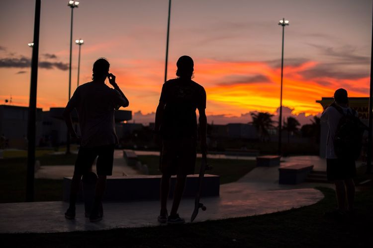 Silhouette people walking at park during sunset