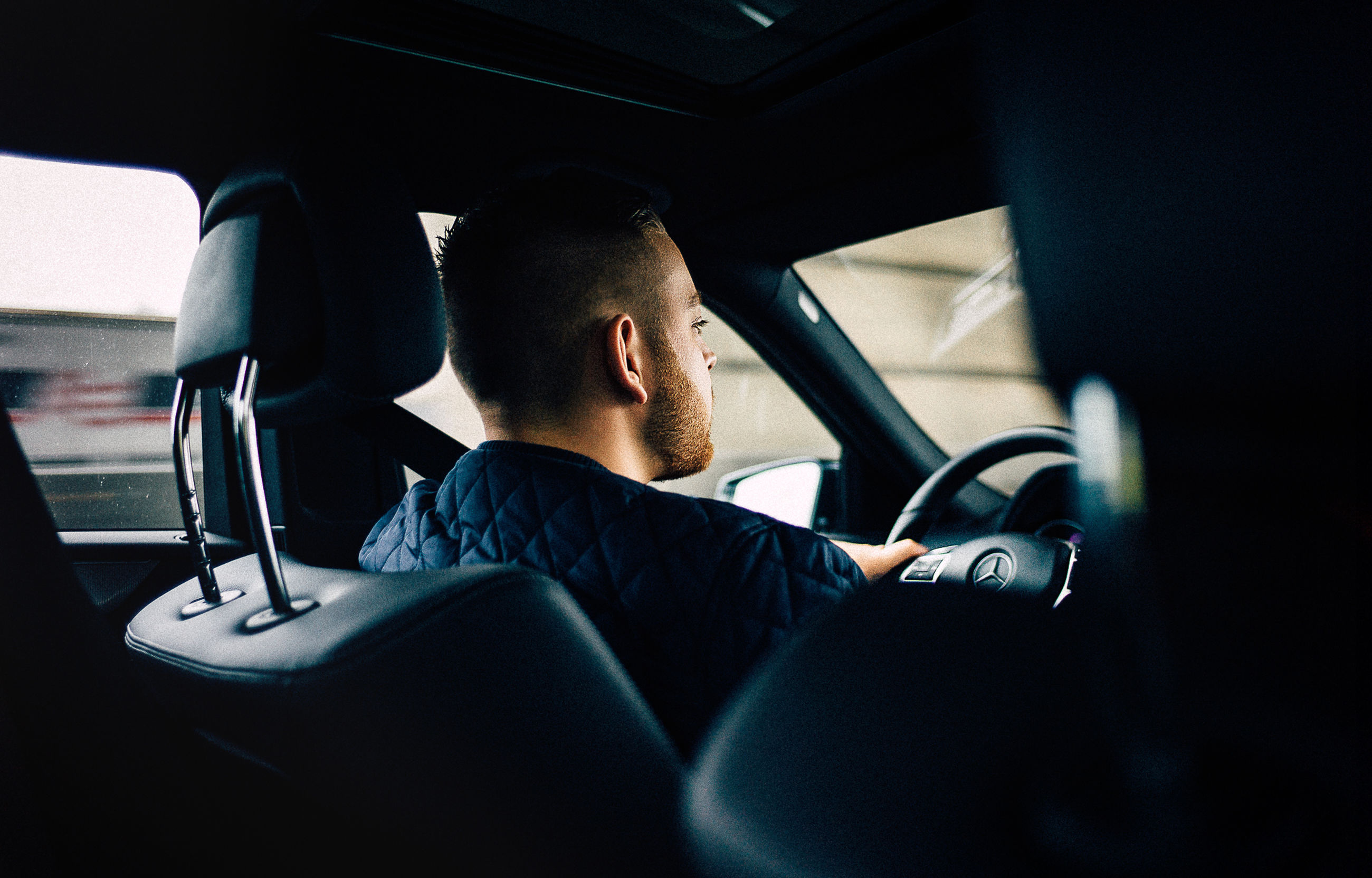 one person, sitting, one man only, only men, car interior, vehicle interior, transportation, adults only, mode of transport, back lit, men, car, adult, people, young adult, businessman, human body part, day, well-dressed, indoors, sky