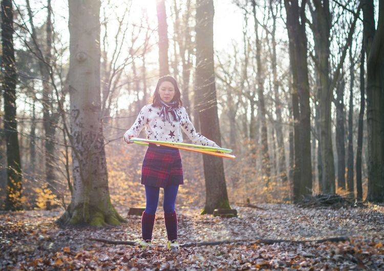 Woman spinning hula hoop while standing on field in forest