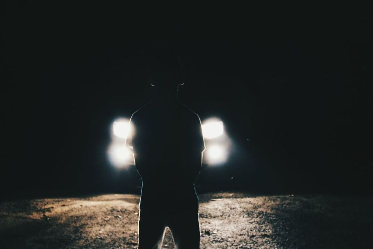 Rear view of silhouette man standing by illuminated car headlights at night