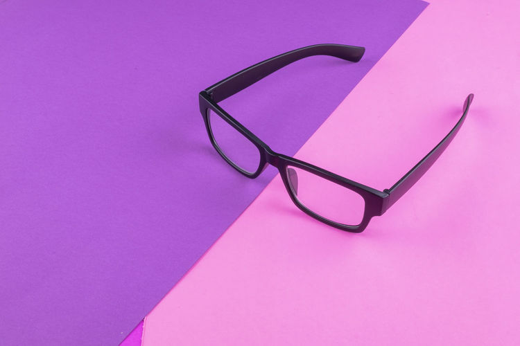 eye glasses spectacles with shiny black frame on pastel color background Pink Color Glasses Eyeglasses  Indoors  Still Life No People Close-up Purple Eyesight Single Object Colored Background Personal Accessory Copy Space Table High Angle View Pink Background Studio Shot Healthcare And Medicine Vision Side View
