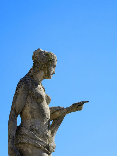 Marble woman sculpture over blue sky background Art Art And Craft Blue Clear Sky Copy Space Day Indicate Low Angle View No People Outdoors Point At Renaissance Sculpture Sky Statue Woman