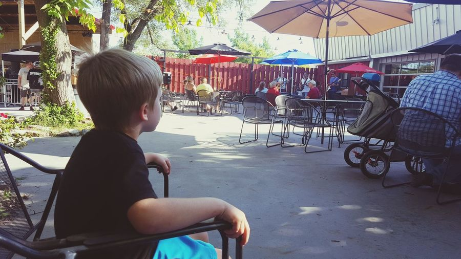 Side view of boy sitting on table at cafe