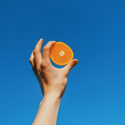 Close-up of hand holding apple against blue sky