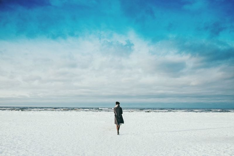 Woman standing at baltic seashore against cloudy sky during winter
