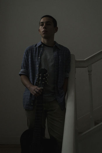 Young man looking away against wall at home