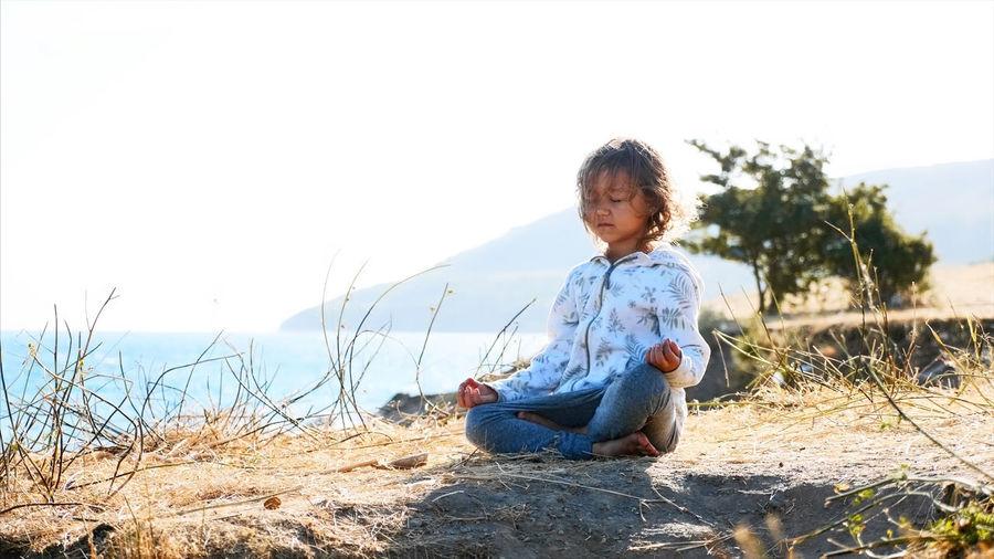 Full length of girl sitting on land against sky