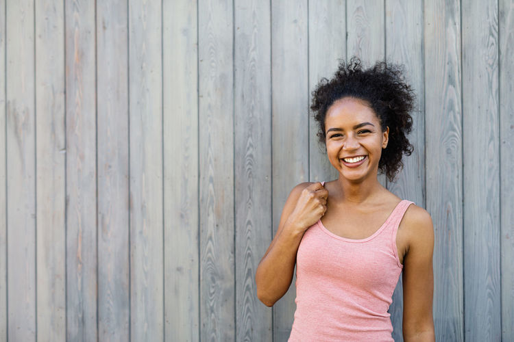 Portrait Of Cheerful Young Woman Standing Against Gray Wooden Wall
