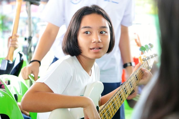 Singing Traning Bass Guitar EyeEm Selects Plucking An Instrument Musical Instrument Child Guitar Musician Portrait Music Playing Girls Healthy Lifestyle Independent School Classroom