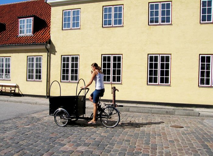 Woman riding cargo bike on street against buildings during sunny day
