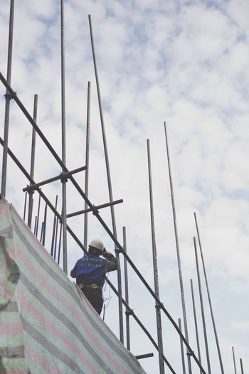 Low Angle View Of Man Standing On Scaffolding Against Sky