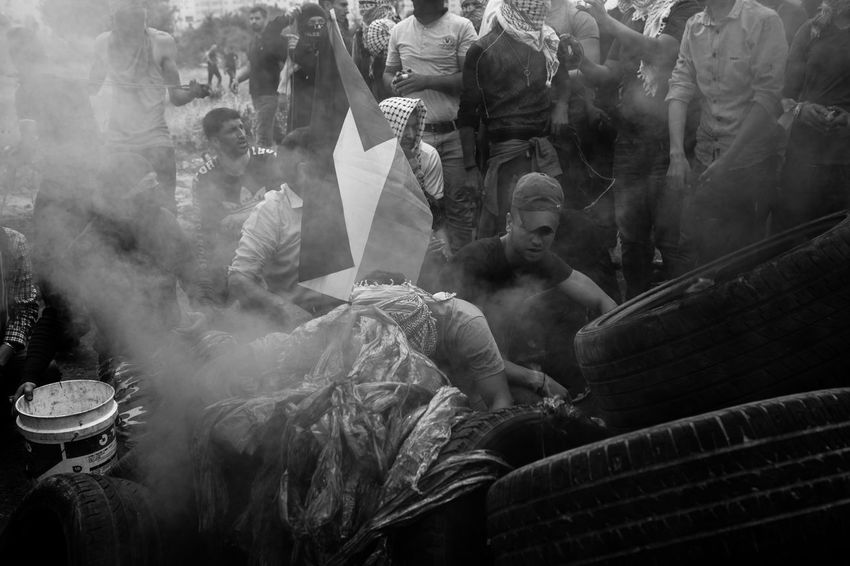 People hiding behind the smoke in Ramallah during clashes for Nakba day commemoration, on the 15th of May in Palestine. Middle East The Photojournalist - 2018 EyeEm Awards Adult Architecture Art And Craft Crowd Day Documentary Group Of People Human Representation Journalism Lifestyles Market Men People Place Of Worship Real People Religion Reportage Representation Sculpture Smoke - Physical Structure Statue Women