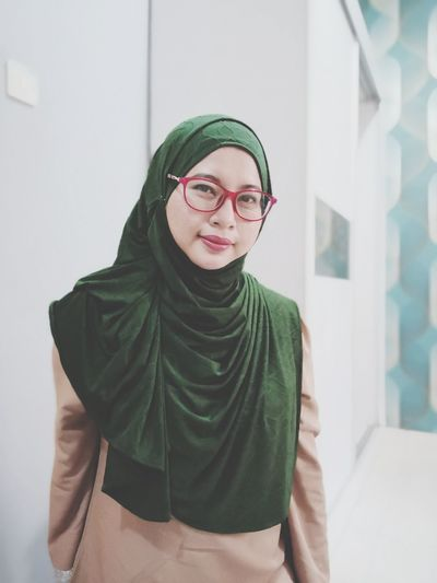 Portrait of smiling woman wearing hijab standing against wall
