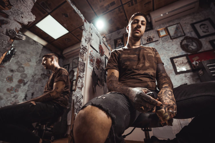Full length of man holding tattoo machine