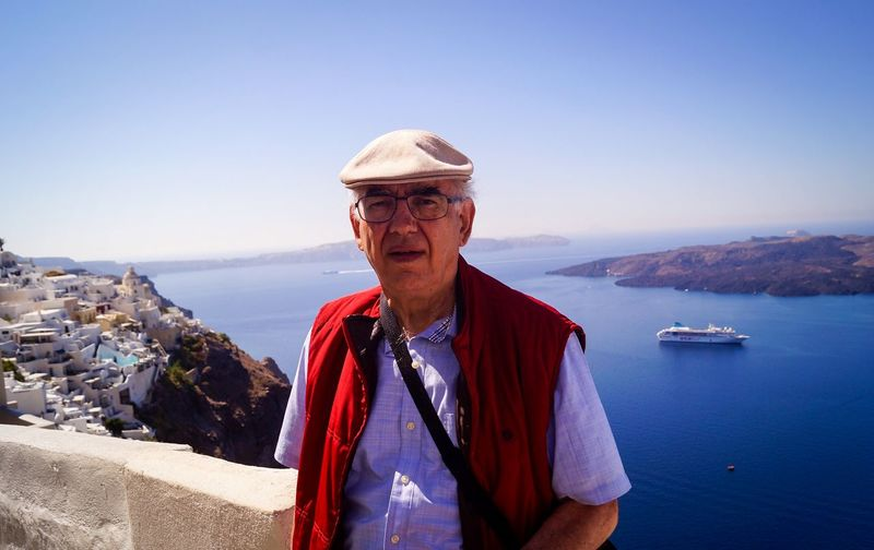 Portrait of senior man with sea in background against clear sky