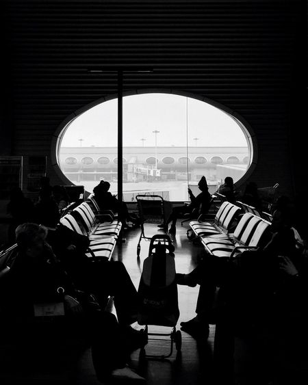 People sitting in departure area against window at chongqing jiangbei international airport