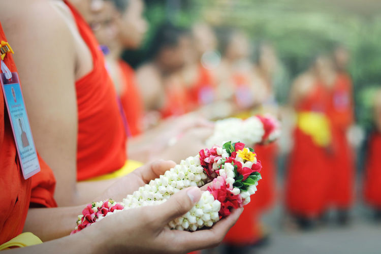 Cropped image of monks holding garland while standing outdoors