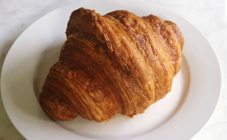 Croissant on a white plate EyeEm Selects Plate Still Life Food And Drink Food Freshness Baked Ready-to-eat Indulgence Croissant French Food Sweet Food Close-up No People High Angle View Brown Serving Size Snack Dessert Indoors  Sweet