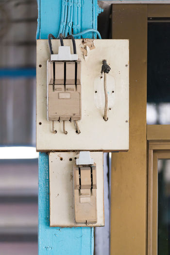 Close-up of telephone booth against wall