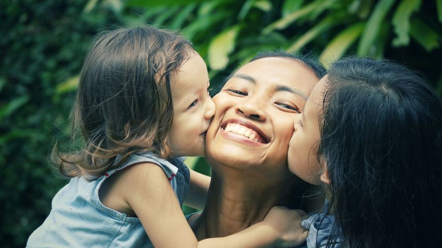 Close-up of girls kissing smiling mother