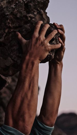 Close-up of man hanging from rock formation