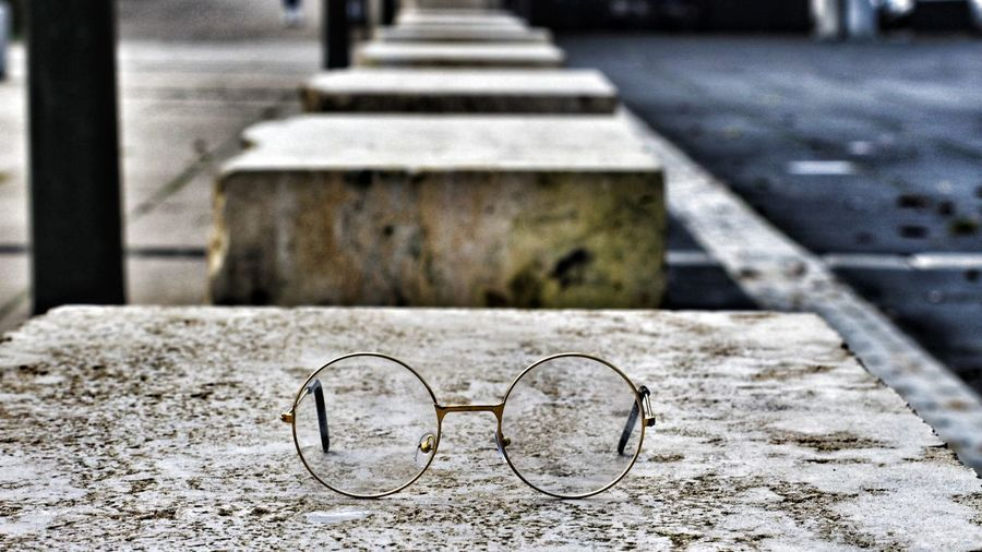 Close-up of eyeglasses on concrete seat