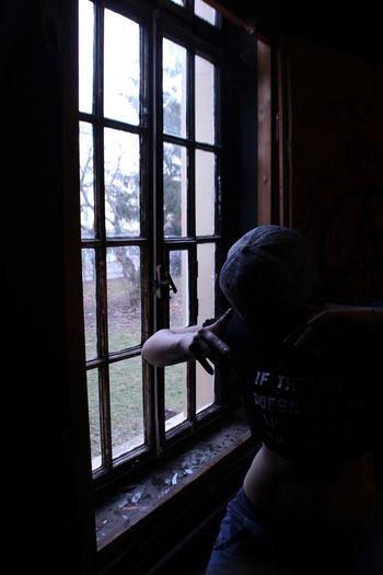 Woman standing by window in darkroom