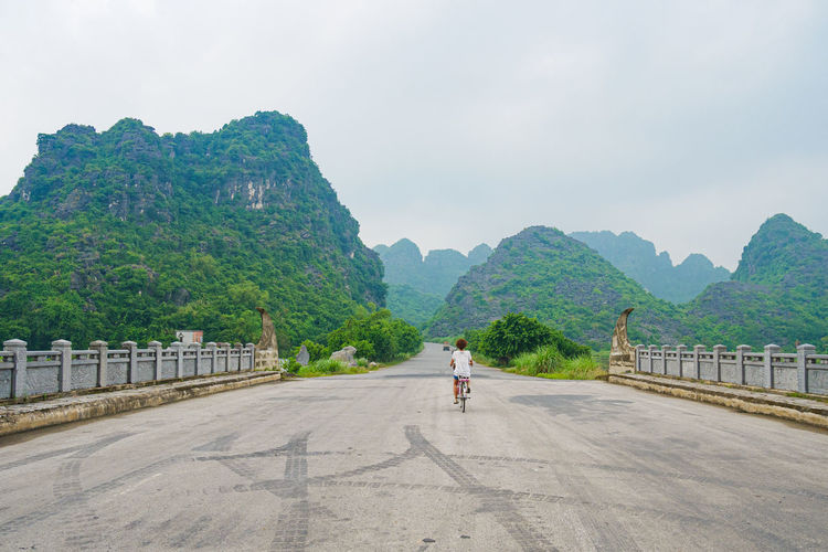 Rear view of person on road by mountains against sky
