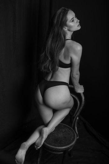 Full length of woman wearing underwear against black background
