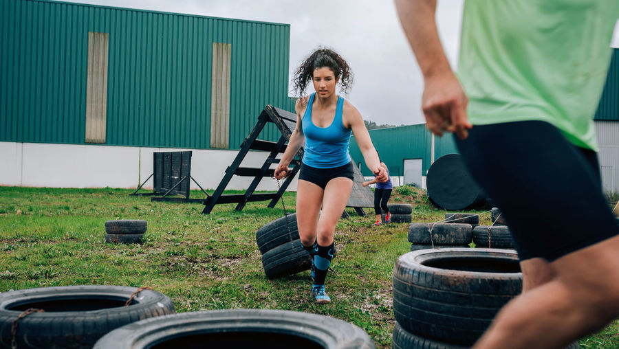Female participant in an obstacle course dragging wheels seen from behind Ocr Obstacle Obstacle Course Race Runner Team Sport Spartan Overcoming Exercise Horizontal Outdoors Extreme Sports Participant Competition Training Hurdle Workout Strong Activity Boot Camp Athlete Effort Grab Real People Caucasian Collaboration Helping Fun Funny Effortless Power Circuit Superation Strength Trying Woman Man Male Female People Dragging Pulling Tire Wheel Sportswear Group Of People Two People Emotion Happiness