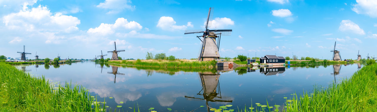 Panoramic view of traditional windmill by lake against sky