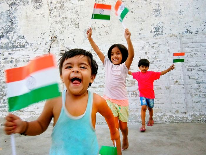 Happy siblings with indian flags running against wall