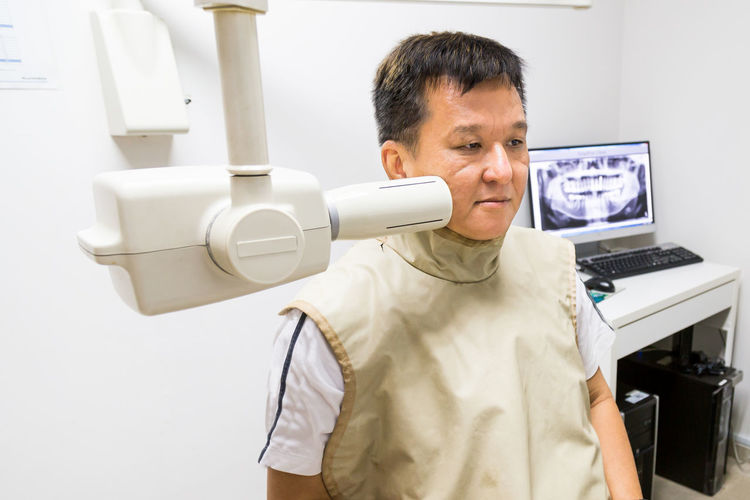 Mature man examined by dental equipment